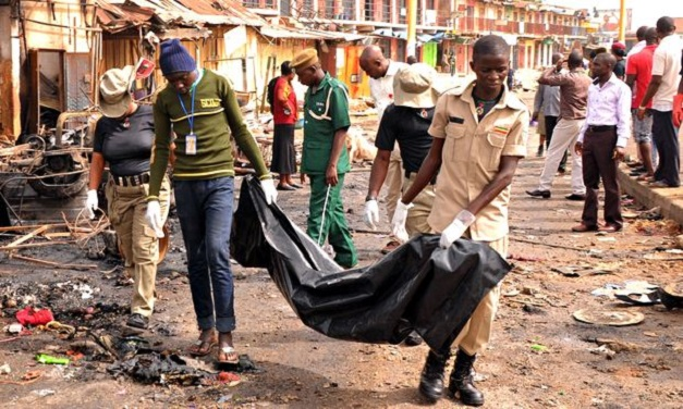 Rescuers carry a body recovered from a shop burned by car bombs in Jos's terminus market
